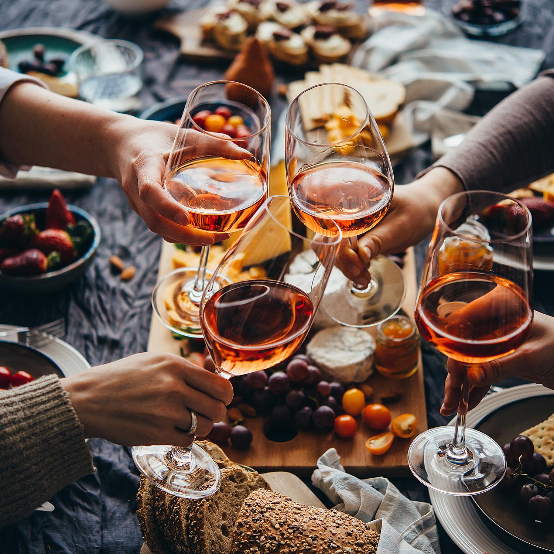Abendessen, Personen stossen mit Weinglas an